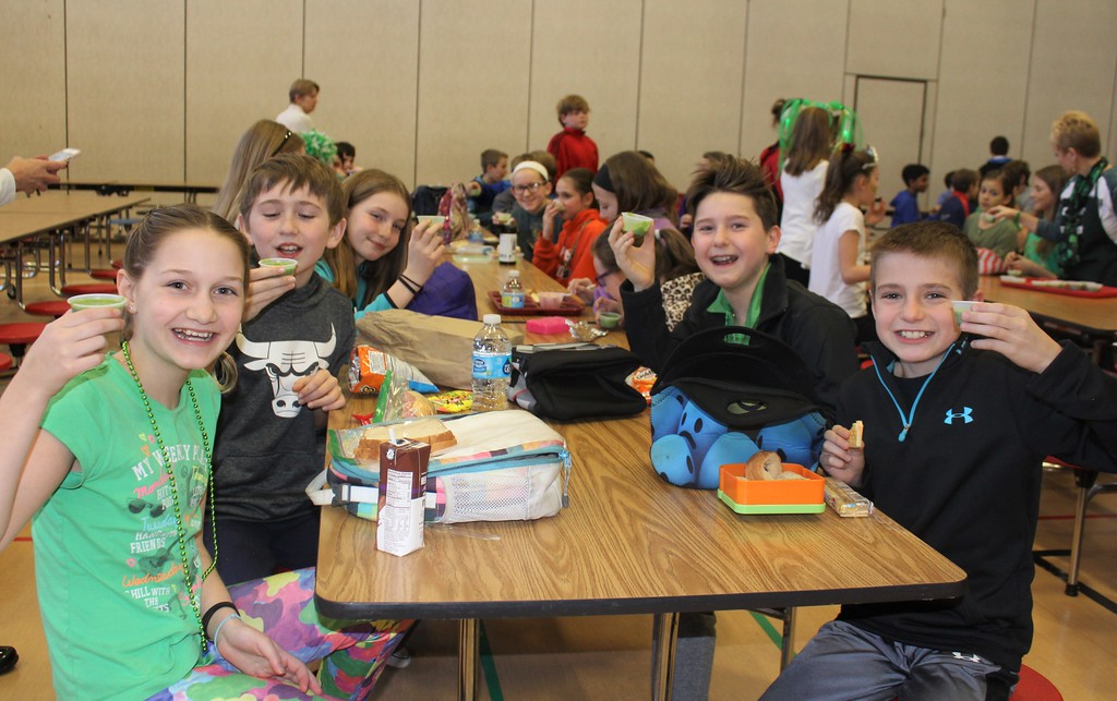 ". East Vincent Elementary students raise healthy and green spinach smoothies during lunch on Friday, March 17, 2017. The school had a ""power up with spinach\"" celebration for St. Patrick\'s Day."