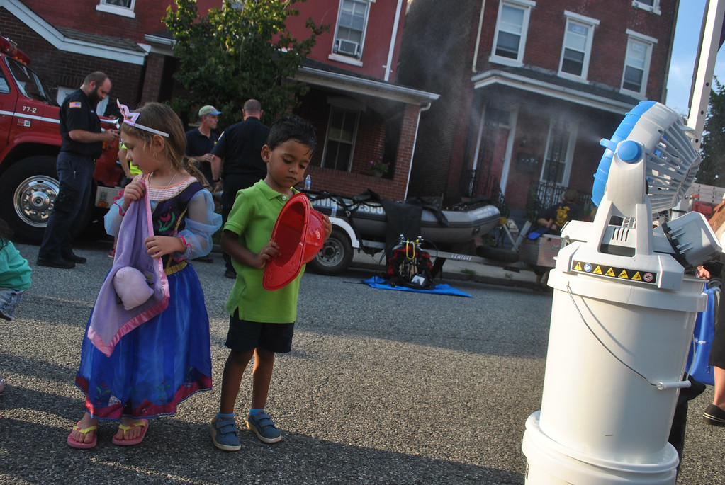 . Cassandra Smith with Victor Chaigneau hit the water fan to keep cool during National Night Out in Phoenixville. Photo by Barry Taglieber � For Digital First Media