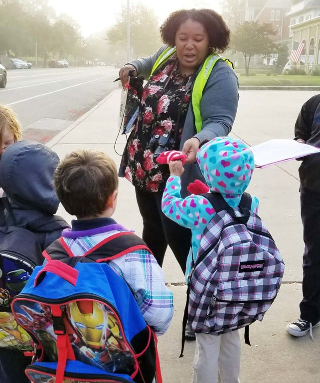 . Michilea Patterson, the new community engagement coordinator for PEAK and a longtime Walking School Bus volunteers, helps one student with her glove Wednesday morning.