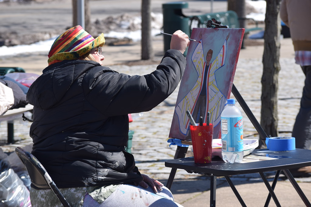 . Marian Dennis � Digital First Media An artist paints a picture in Smith Family Plaza Saturday as kids and families enjoy the downtown egg hunt.