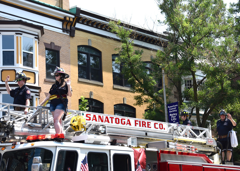 . Jesi Yost � For Digital First Media Members of the Sanatoga Fire Company ride on top one of their firetrucks during Pottstown�s Fourth of July Parade.