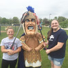 Abigail Krause and Reilly Owens get some lacrosse tips from Trojan Man before a recent practice.