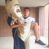 Pottstown High School football player Dreaden Gwimer gives a very tired Trojan Man a lift.