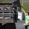 John Strickler - Digital First Media<br /> Raekwon Artley tosses a bag of debris onto a dump truck during the 'Rock the Block' cleanup in Pottstown.