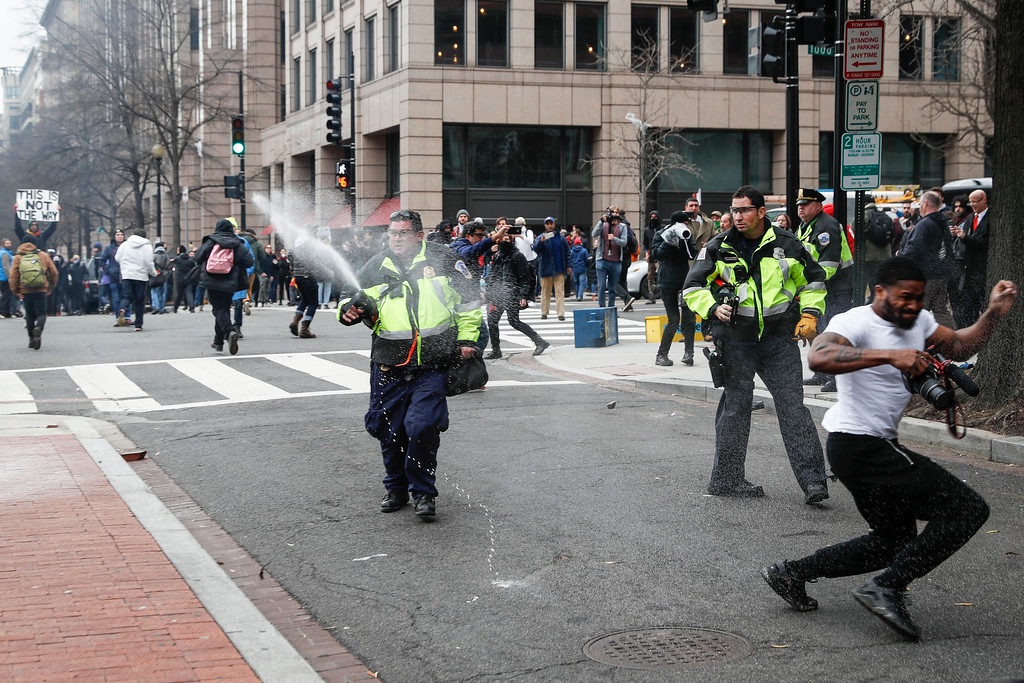 . Police officers fire pepper spray at protesters during a demonstration after the inauguration of President Donald Trump, Friday, Jan. 20, 2017, in Washington. (AP Photo/John Minchillo)