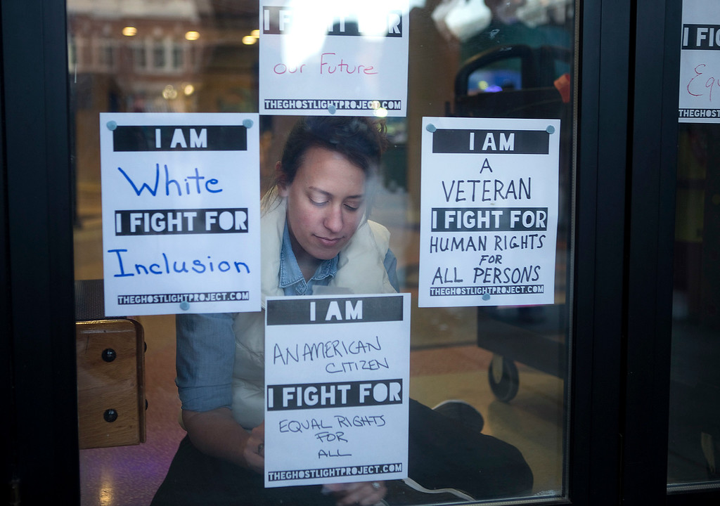 . Alicia Varcoe with Mill Mountain Theatre tapes up pledge cards in the windows of Center in the Square, written by community members attending the launch of The Ghostlight Project, Thursday evening, Jan. 19, 2017, in Roanoke, Va. Hosted by the theatre and simultaneously by theaters across the country, the evening\'s event invited community members to come together with their lights in solidarity to promote inclusion, participation and compassion for all.  (Erica Yoon/The Roanoke Times via AP)