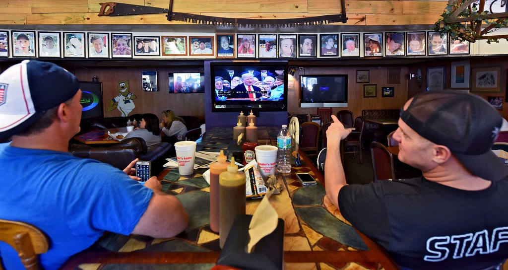 . Stuart Lackey (from left) and Ritch Ludke picked a spot right down front to watch the Inauguration of Donald J. Trump as the 45th President of the United States as they sat in Angie\'s Subs in Jacksonville Beach, Fla., on Friday, Jan. 20, 2017. (Bob Mack /The Florida Times-Union via AP)