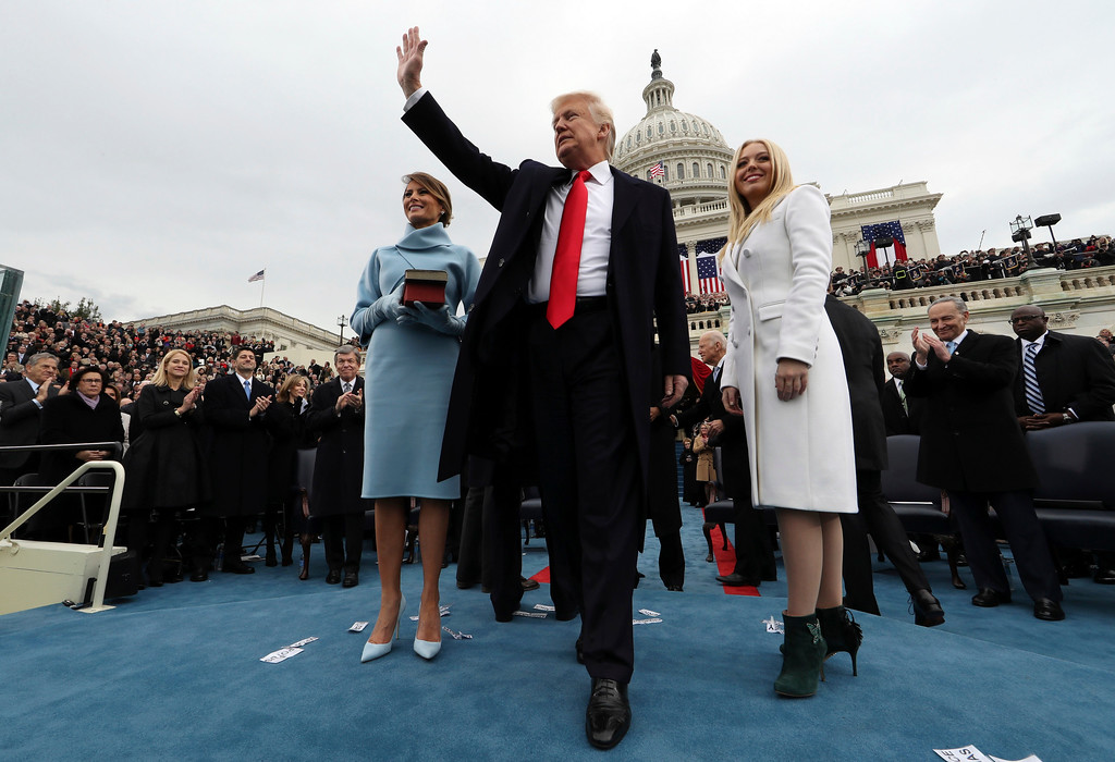 . President Donald Trump waves after taking the oath of office as his wife Melania holds the Bible, and Tiffany Trump looks out to the crowd, Friday, Jan. 27, 2017 on Capitol Hill in Washington. (Jim Bourg/Pool Photo via AP)
