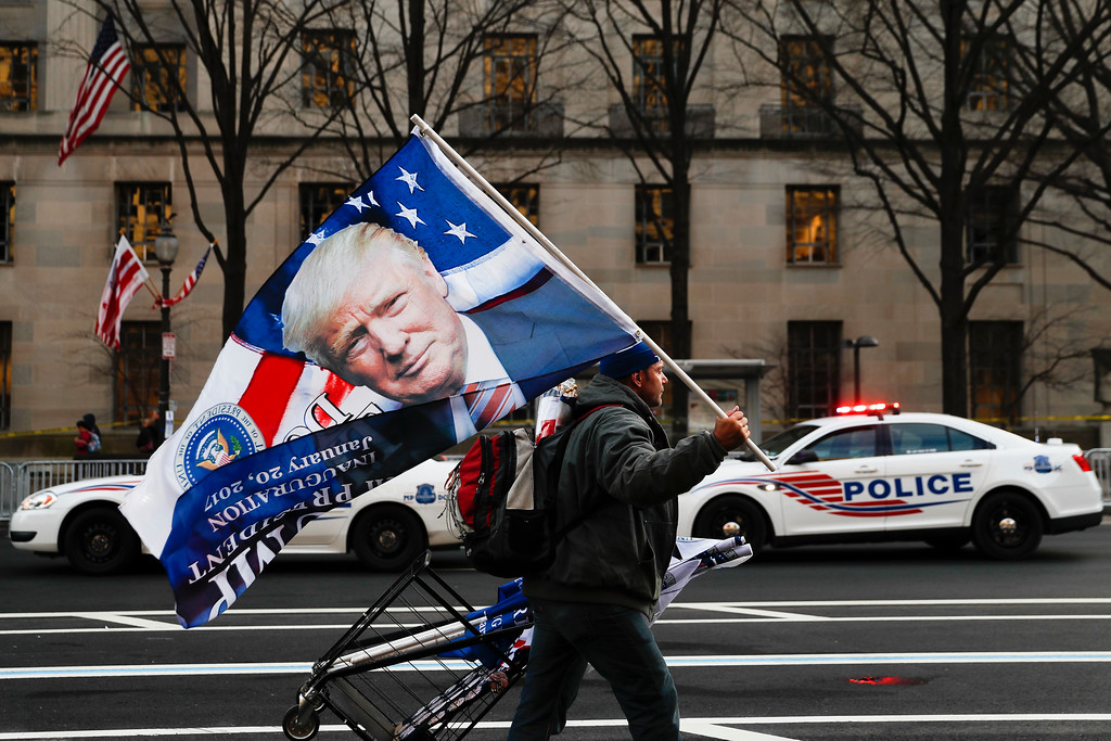 . A street vendor holds a flag bearing the likeness of President-elect Donald Trump as he passes a line of police vehicles on Pennsylvania Avenue in Washington, Thursday, Jan. 19, 2017, ahead of Friday\'s presidential inauguration. (AP Photo/John Minchillo)