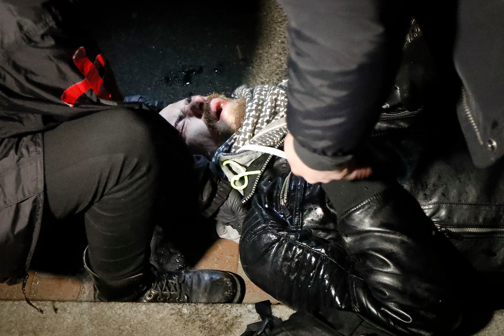 . A protester winces in pain after being pepper sprayed by police during a protest ahead of the presidential inauguration, Thursday, Jan. 19, 2017, in Washington. (AP Photo/John Minchillo)