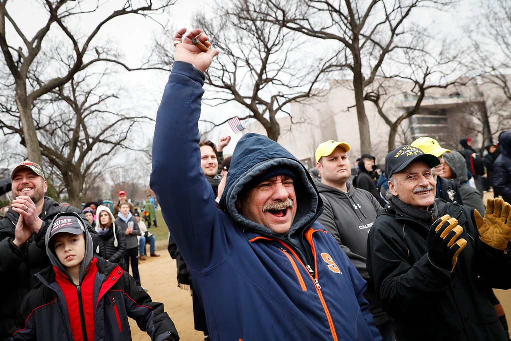 ". A supporter cheers President-elect Donald Trump declares his inauguration ""remembered as the day the people became the rulers of this nation again,\"" Friday, Jan. 20, 2017, in Washington. (AP Photo/John Minchillo)"