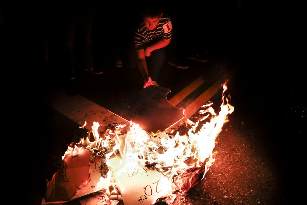 . A young protestor feeds a fire of protest signs during a demonstration outside the National Press Building ahead of the presidential inauguration, Thursday, Jan. 19, 2017, in Washington. (AP Photo/John Minchillo)