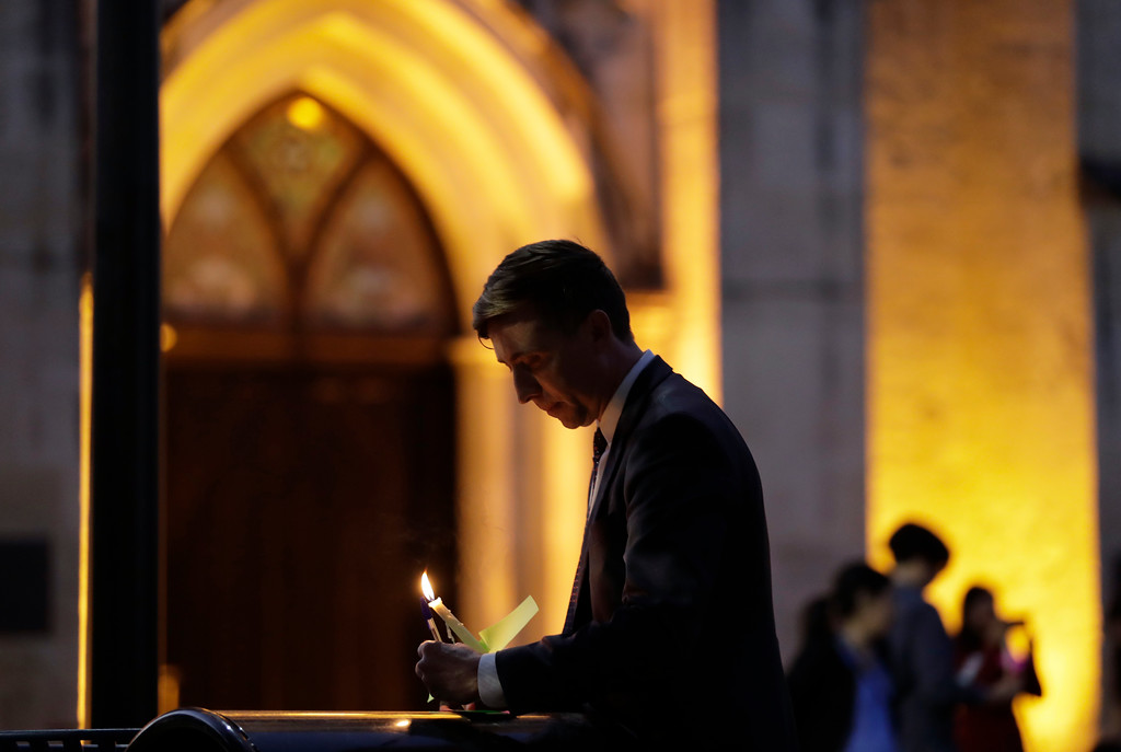 . Jonathan Ryan writes a note of home as he joins other community activists in front of San Fernando Cathedral for a vigil on the eve of President-elect Donald Trump\'s inauguration, Thursday, Jan. 19, 2017, in San Antonio. The group gathered to show their support for immigration groups, women\'s groups, minorities, and others they fear may be harmed by the new administration\'s policies. (AP Photo/Eric Gay)