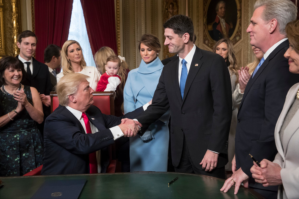 . President Donald Trump turns to House Speaker Paul Ryan as he is joined by the Congressional leadership and his family as he formally signs his cabinet nominations into law, in the President\'s Room of the Senate, at the Capitol in Washington, Friday, Jan. 20, 2017. (AP Photo/J. Scott Applewhite, Pool)