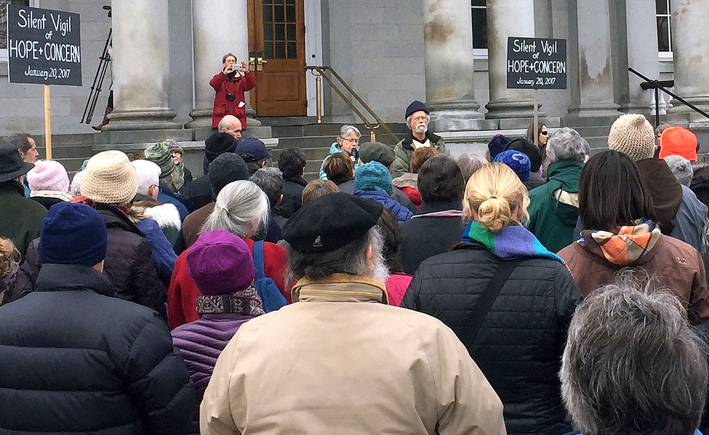 . The Revs. Leanne Tigert, at microphone, and Gray Fitzgerald, wearing hat, lead a vigil in front of the New Hampshire Statehouse in Concord, N.H., before President Donald Trump\'s inauguration Friday, Jan. 20, 2017 in Washington. The two read a prayer before asking the crowd to silently reflect for ten minutes through. (AP Photo/Kathleen Ronayne)