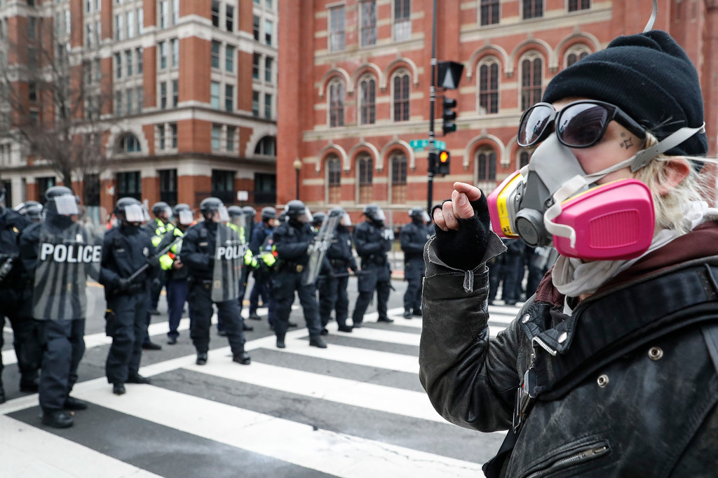 . A protester faces off with a line of riot police during a demonstration after the inauguration of President Donald Trump, Friday, Jan. 20, 2017, in Washington. (AP Photo/John Minchillo)