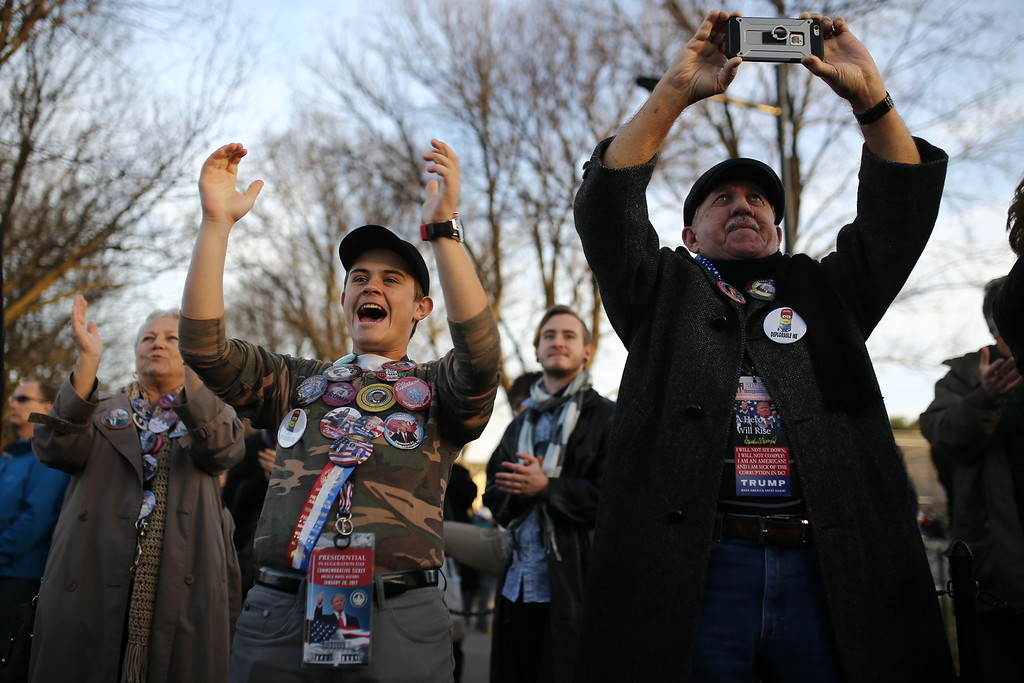 . Brandon Maly, 17, of Tampa and Dan Schramik of St. Petersburg, Fla. react to Donald Trump\'s appearance at a free concert on the grounds of the Lincoln Memorial and the Reflecting Pool on Thursday, Jan. 19, 2017. Schramik was a co-chair to the Hillsborough County Donald Trump campaign and Brandon was an active participant in campaigning. Dan and Amy have been married for 48 years. This was the first time to get involved in a campaign. Maly is a senior at King High School in Tampa. (Charlie Kaijo/The Tampa Bay Times via AP)