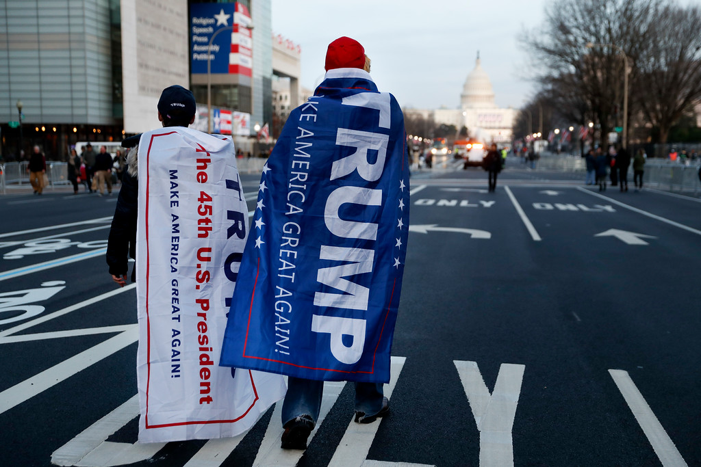 . Supporters of President-elect Donald Trump walk along Pennsylvania Avenue after it was closed down to thru-traffic as security tightens ahead of the presidential inauguration, Thursday, Jan. 19, 2017, in Washington. (AP Photo/John Minchillo)