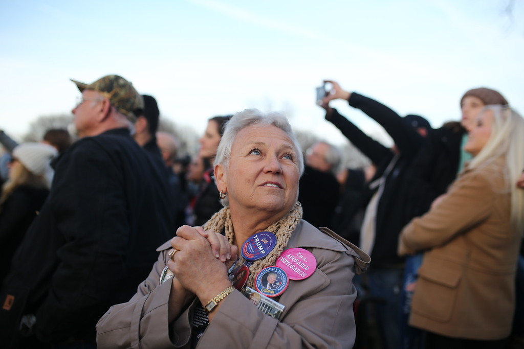 ". Amy Schramik of St. Petersburg, Fla. reacts to Donald Trump\'s appearance at a free concert on the grounds of the Lincoln Memorial and the Reflecting Pool on Thursday, January 19, 2017. Schramik was an assistant co-chair to the Hillsborough County Donald Trump Campaign. Formerly a Democrat, she converted to Republic in January 2015 so she could vote to nominate Trump. ""I honestly think he\'s going to try to deliver what he promised. Deliver on his promises. Jobs. I\'m not sure how much a president can do about jobs. The businesses are out there or they\'re not. He\'s got to come through on his promises,\"" she said. (Charlie Kaijo/The Tampa Bay Times via AP)"
