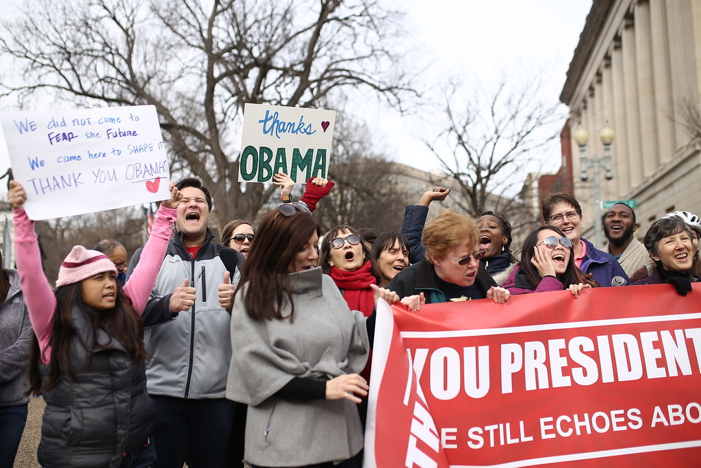 ". A group holding signs chant, ""Thank you Obama!\"" at Lafayette Park outside of The White House in Washington D.C. on Thursday January 19, 2017 (Charlie Kaijo/The Tampa Bay Times via AP)"