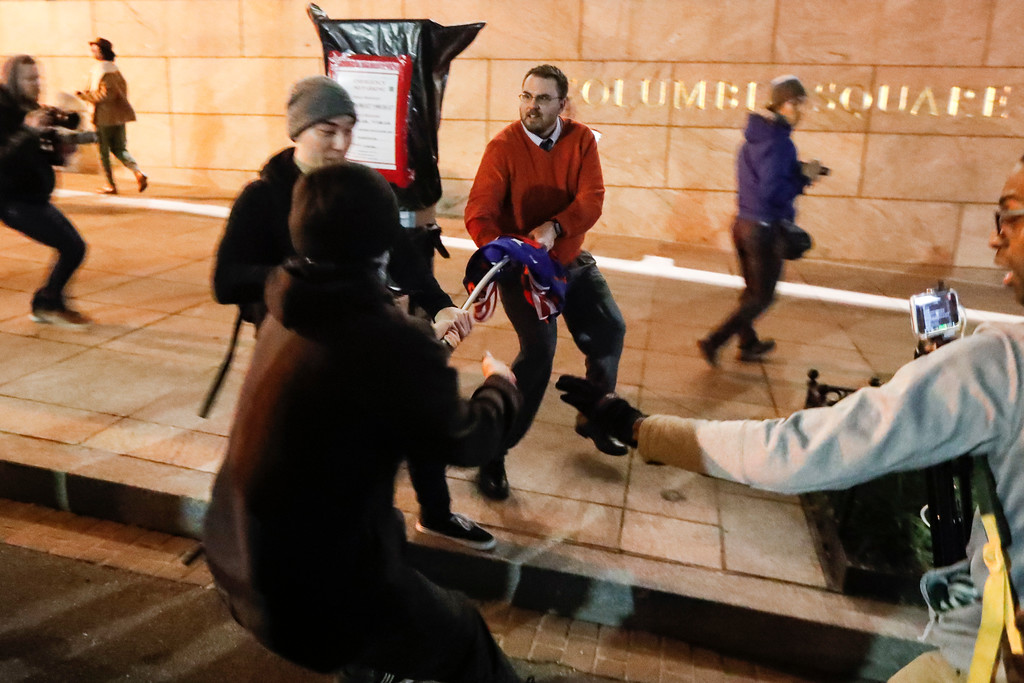 . Protesters battle over Trump supporters campaign flag ahead of the presidential inauguration, Thursday, Jan. 19, 2017, in Washington. (AP Photo/John Minchillo)