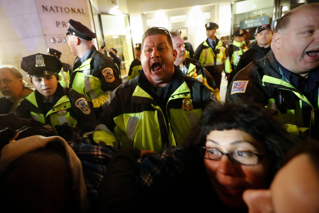 . A police officer yells for protesters to step off the sidewalk ahead of the presidential inauguration, Thursday, Jan. 19, 2017, in Washington. (AP Photo/John Minchillo)