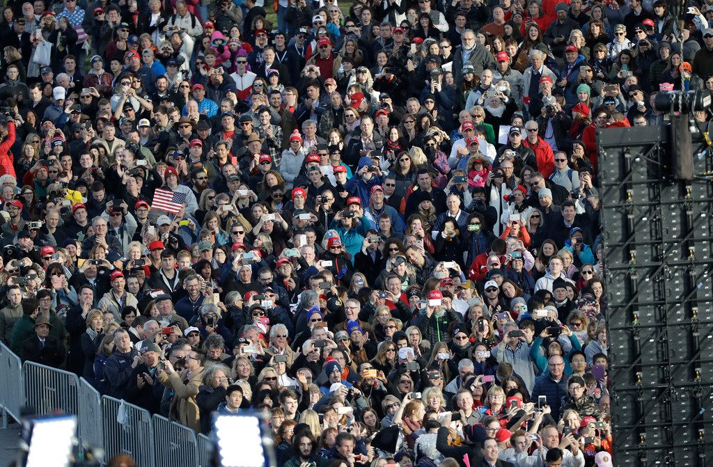 """. People watch video monitor showing President-elect Donald Trump laying a wreath at the Tomb of the Unknowns at Arlington National Cemetery before the start of a pre-Inaugural \""""Make America Great Again! Welcome Celebration\"""" at the Lincoln Memorial in Washington, Thursday, Jan. 19, 2017. (AP Photo/David J. Phillip)"""