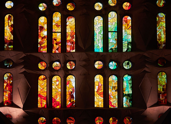On one side of Barcelona's Sagrada Familia the stained glass windows take advantage of the setting sun, with warm reds, oranges and yellows. The other side refelcts cool morning colours of green and blue