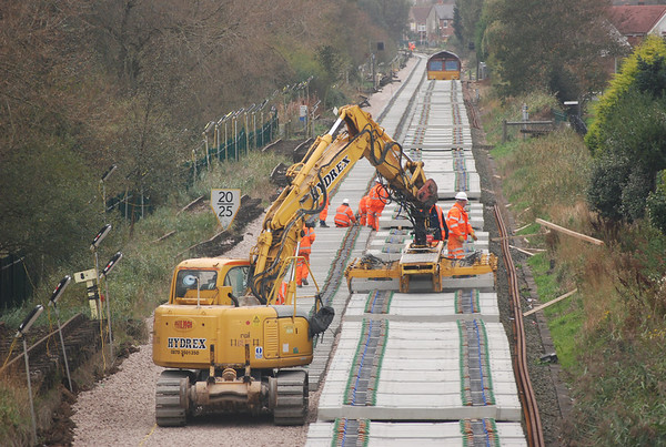 Hydrex Road Railer 911132-7 pics up a load of sleepers severn in total with the mechanical grab attachment