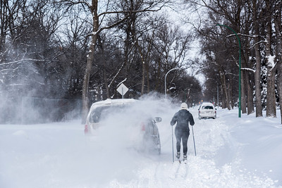 A van gets stuck in the snow, as Mel Dupuis skis down a residential street in River Heights in Winnipeg following a Boxing Day winter storm December 26, 2016.