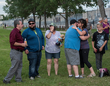 Close friends and family console each other during a vigil type event on the one year anniversary of Thelma Krull's disappearance at Civic Park Monday July 11, 2016 (Thelma's husband Robert is pictured far left). (David Lipnowski for Metro News)