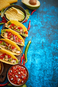 Fresh Mexican tacos with chicken meat, jalapeno, fresh vegetables served with guacamole and tomato s