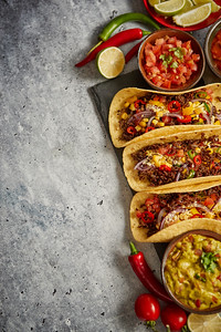 Tasty Mexican meat tacos served with various vegetables and salsa. With sides in ceramic bowls aroun