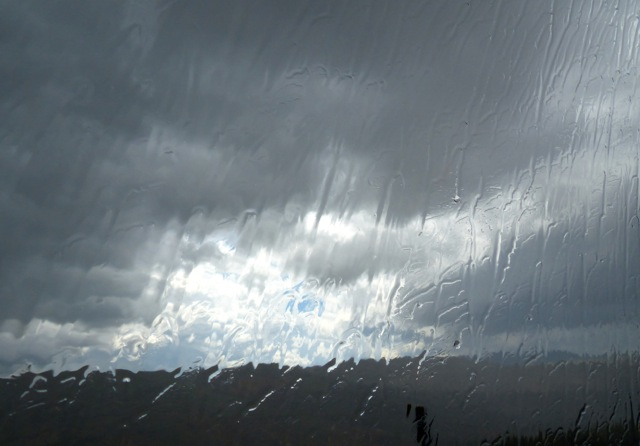 Storm clouds through heavy rain on bus window.