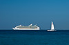 A cruise ship and sailboat in the Caribbbean sea offshore Cozumel, Mexico.