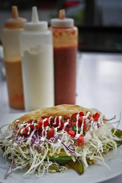 A taco with salsas and sour cream.