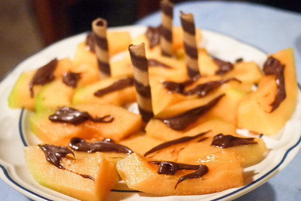 Creative dessert with melon, nutellas, and pirouettes.
