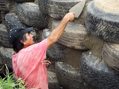 Worker Filling in Gaps between Tires Used as Building Material