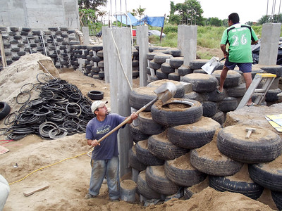 Construction Worker Shovels Sand into Used Tire - 1
