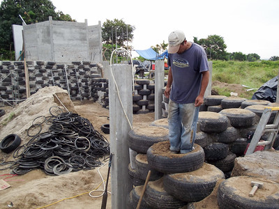 Construction Worker Standing on Wall being Made from Used Tires