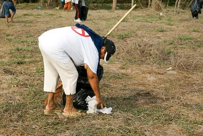 Woman Picking Up Litter in Field