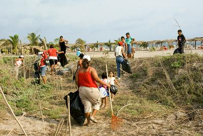 Community Volunteers with Rakes and Bags Clean Up Garbage by Beach