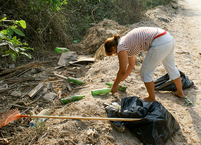 Woman Picks up Glass Bottles Garbage by Roadside