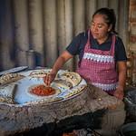 Woman teaching how she makes empanadas de mole amarillo for an EnVia tour.