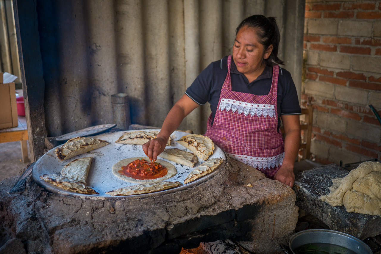 Woman teaching how she makes empanadas de mole amarillo for an EnVia tour.