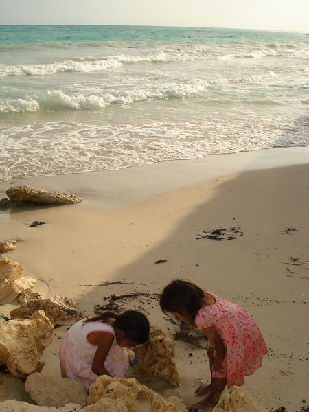 These two girls were rummaging through the garbage that the waves had washed up. They were playing with anything they could find.