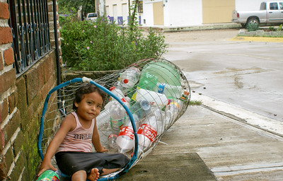 Overturned Plastic Bottle Collection Basket and Young Mexican Girl