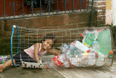 Young Mexican Girl Playing in a Recycling Basket