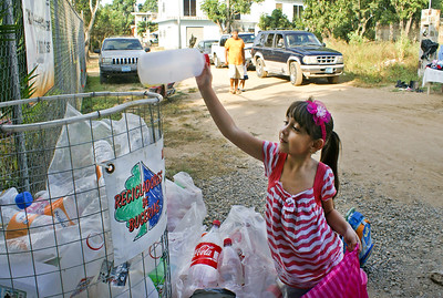 Mexican Schoolgirl Puts Plastic Bottle into Recycling Container