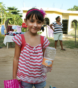 Girl Brings Used Plastic Bottles to School for Recycling
